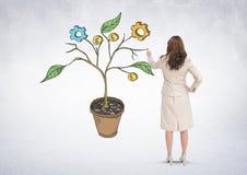 La penna di tenuta della donna ed il disegno dei grafici dell'attività sulla pianta si ramifica sulla parete Fotografie Stock