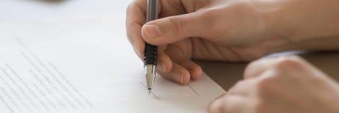 La penna di tenuta maschio della mano del primo piano ha messo la firma sul documento ufficiale fotografia stock