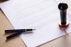 La penna ed il metallo del pubblico del notaio timbrano sul testamento Immagine Stock Libera da Diritti