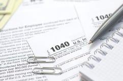 La penna, il taccuino e le banconote in dollari è bugie sulla forma 1040 di imposta Fotografia Stock Libera da Diritti