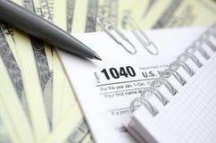 La penna, il taccuino e le banconote in dollari è bugie sulla forma 1040 di imposta Fotografia Stock