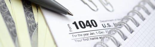 La penna, il taccuino e le banconote in dollari è bugie sulla forma 1040 di imposta Immagine Stock