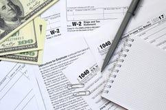 La penna, il taccuino e le banconote in dollari è bugie sulla forma 1040 di imposta Fotografie Stock