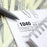 La penna, il taccuino e le banconote in dollari è bugie sulla forma 1040 di imposta Immagini Stock