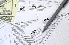 La penna, il taccuino e le banconote in dollari è bugie sulla forma 1040 di imposta Fotografie Stock Libere da Diritti