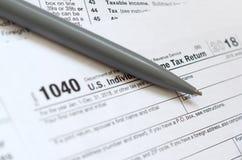 La penna si trova sulla forma di imposta U 1040 S L'imposta sul reddito delle persone fisiche macera Immagini Stock