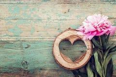 La peonía rosada y el corazón tallados en madera en el viejo grunge pintaron a BO Imágenes de archivo libres de regalías