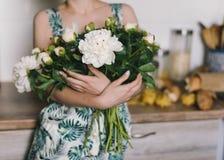 La peonia sveglia ed adorabile fiorisce in mani del ` s delle donne Molti petali stratificati Fondo grigio chiaro dei fiori bianc Immagine Stock