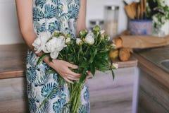 La peonia sveglia ed adorabile fiorisce in mani del ` s delle donne Molti petali stratificati Fondo grigio chiaro dei fiori bianc Fotografie Stock