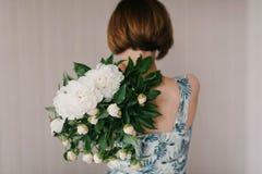 La peonia sveglia ed adorabile fiorisce in mani del ` s delle donne Molti petali stratificati Fondo grigio chiaro dei fiori bianc Immagini Stock Libere da Diritti