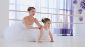 La pequeña bailarina en el tutú blanco está estirando en actitud de la rana con el profesor del ballet almacen de video