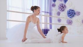 La pequeña bailarina hace actitud de la rana del ejercicio del estiramiento con su profesor en la lección almacen de video