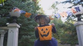 La pequeña bruja lleva a cabo truco o el bolso de la invitación, pide dulces al aire libre, partido de Halloween almacen de metraje de vídeo