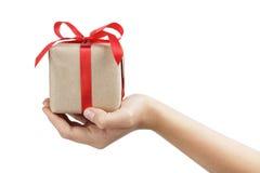 La pequeña caja de regalo wraped en papel reciclado con el arco de la cinta en la mano adolescente femenina Fotografía de archivo