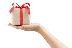 La pequeña caja de regalo wraped en papel reciclado con el arco de la cinta en la mano adolescente femenina Imágenes de archivo libres de regalías