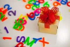 La pequeña caja de regalo y el alfabeto colorido del ABC bloquean letras plásticas, Foto de archivo libre de regalías
