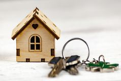 La pequeña casa al lado de ella es las llaves Símbolo de emplear una casa para el alquiler, vendiendo un hogar, comprando un hoga fotos de archivo libres de regalías