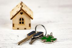 La pequeña casa al lado de ella es las llaves Símbolo de emplear una casa para el alquiler, vendiendo un hogar, comprando un hoga foto de archivo