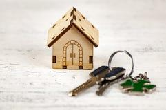 La pequeña casa al lado de ella es las llaves Símbolo de emplear una casa para el alquiler, vendiendo un hogar, comprando un hoga Imagen de archivo libre de regalías