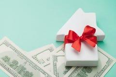 La pequeña casa blanca adornó la cinta roja del arco y dólares de dinero en fondo verde Compra de un nuevo hogar, regalo o venta  Foto de archivo