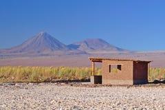 La pequeña casa de adobe en el desierto en terreno de la sal y acerca a dos vol. Imagen de archivo libre de regalías