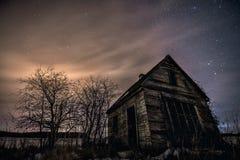 La pequeña casa de madera abandonada vieja en la noche con el brillo protagoniza Foto de archivo libre de regalías