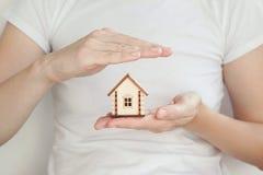 La pequeña casa de madera en mano del ` s de las mujeres, una mano protege el tejado de la casa imagen de archivo