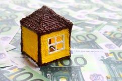 La pequeña casa del juguete es mentiras en un sistema de denominaciones monetarias verdes fotos de archivo libres de regalías