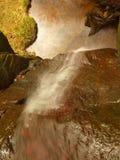 La pequeña cascada en pequeña corriente de la montaña, bloque cubierto de musgo de la piedra arenisca y el agua está saltando abaj Fotos de archivo libres de regalías