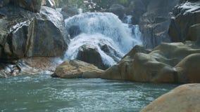 La pequeña cascada espumosa corre en el lago entre rocas almacen de metraje de vídeo