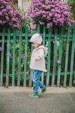 La pequeña chica joven huele una flor en un fondo del FE verde Fotografía de archivo