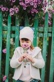 La pequeña chica joven huele una flor en un fondo del FE verde Foto de archivo libre de regalías