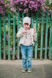 La pequeña chica joven huele una flor en un fondo del FE verde Imagen de archivo