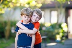 La pequeña escuela activa dos embroma los muchachos, los gemelos y a los hermanos abrazando el día de verano Foto de archivo libre de regalías