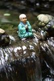 La pequeña estatua del monje de Buda se está sentando en el medio de la cascada Foto de archivo libre de regalías