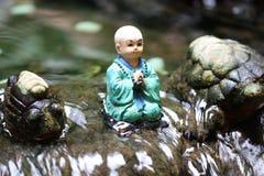 La pequeña estatua del monje de Buda se está sentando en el medio de la cascada Fotografía de archivo