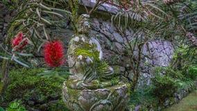 La pequeña estatua encontró en la tranquilidad de un jardín japonés Foto de archivo