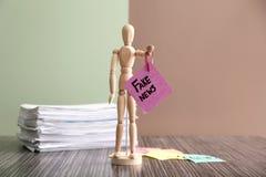 La pequeña figura humana que sostiene la hoja de papel con las palabras FALSIFICA NOTICIAS en la tabla de madera fotografía de archivo libre de regalías
