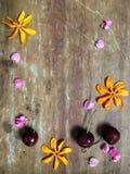 La pequeña flor y la fruta fresca arreglan en el fondo de madera Fotos de archivo
