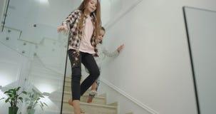 La pequeña hermana feliz y carismática y la grande en el plumón que viene divertido de la mañana a las escaleras consiguen li