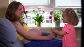 La pequeña hija cuidadosa le trae el vidrio embarazada de la madre de agua almacen de metraje de vídeo