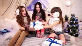La pequeña hija da los presentes de Santa Claus, sorpresa para las chicas jóvenes, la Navidad del Año Nuevo del intercambio de tr almacen de metraje de vídeo