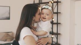 La pequeña hija en el ` s de la madre arma en casa Madre sonriente con el bebé metrajes