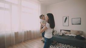 La pequeña hija en el ` s de la madre arma en casa Madre sonriente con el niño almacen de video