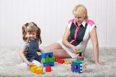 La pequeña hija feliz y su madre embarazada juegan los juguetes Foto de archivo