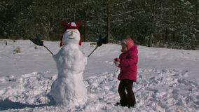La pequeña hija hace un muñeco de nieve en el prado cerca del bosque metrajes