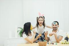 La pequeña hija linda con las coletas y los oídos del conejito está abrazando a sus padres Madre y padre que pintan los huevos de fotografía de archivo