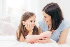 La pequeña hija satisfecha mira curiosamente su madre que lea cuento de hadas, sostenga el pequeño libro, cama cómoda de OM de la foto de archivo libre de regalías