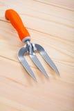 La pequeña mano de la herramienta que cultiva un huerto bifurca en los tableros de madera imagen de archivo libre de regalías