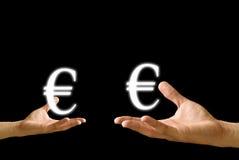 La pequeña mano y la mano grande tienen icono euro de Imagen de archivo